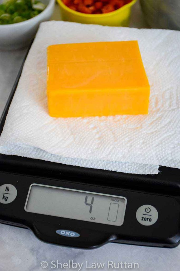 4 oz brick of cheddar cheese on a food scale
