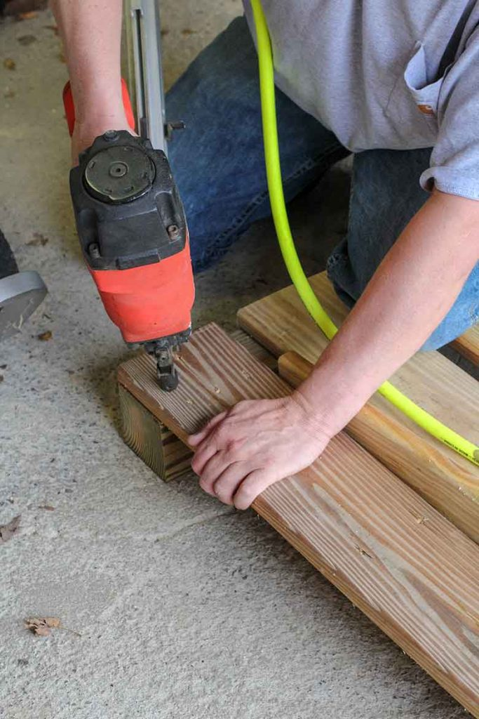 Using a air pressure nailer to attach the boards together