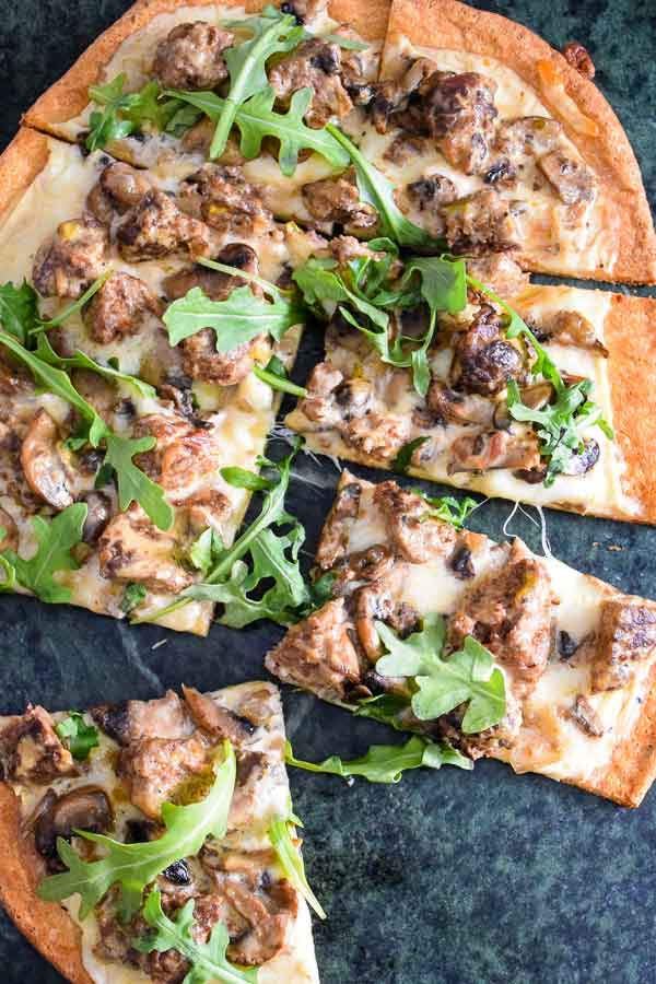 Venison Meatball Pizza with Alfredo Sauce and Arugula cut in slices