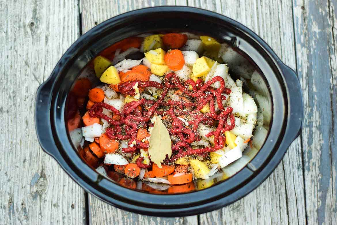 Overhead view of vegetables  and seasoning in slow cooker