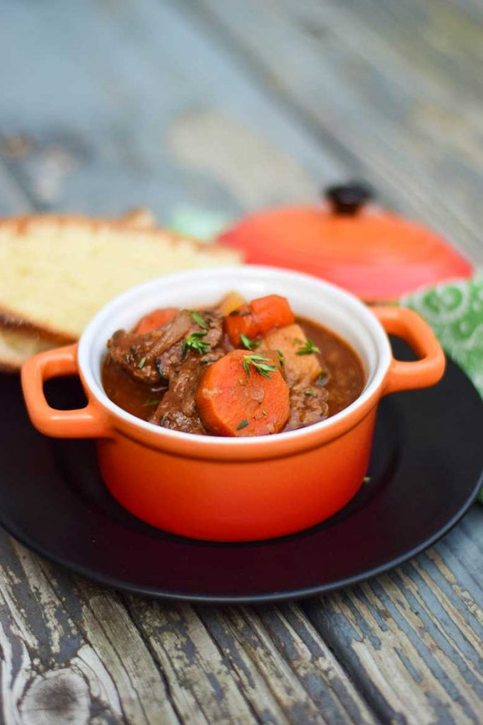 Side view of crockpot venison stew in serving bowl with two slices of bread in background