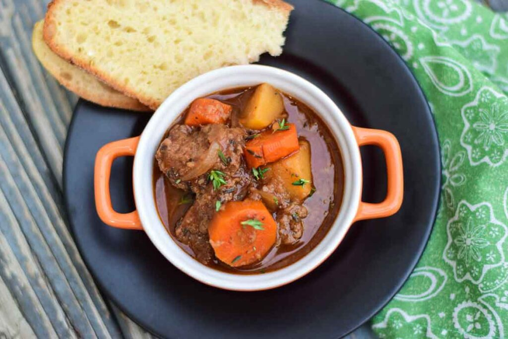 Crockpot Venison Stew in an orange crock with two slices of homemade bread on a black plate and green and white napkin