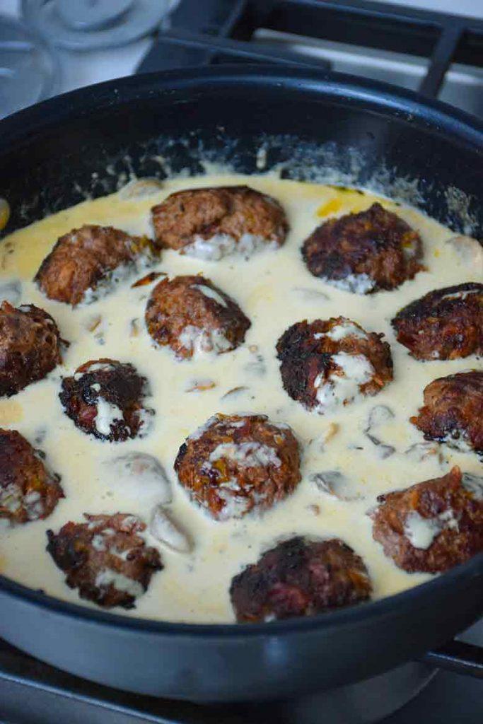 venison meatballs simmering in alfredo sauce