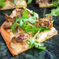 Venison Meatball Pizza with Alfredo Sauce and Arugula sliced