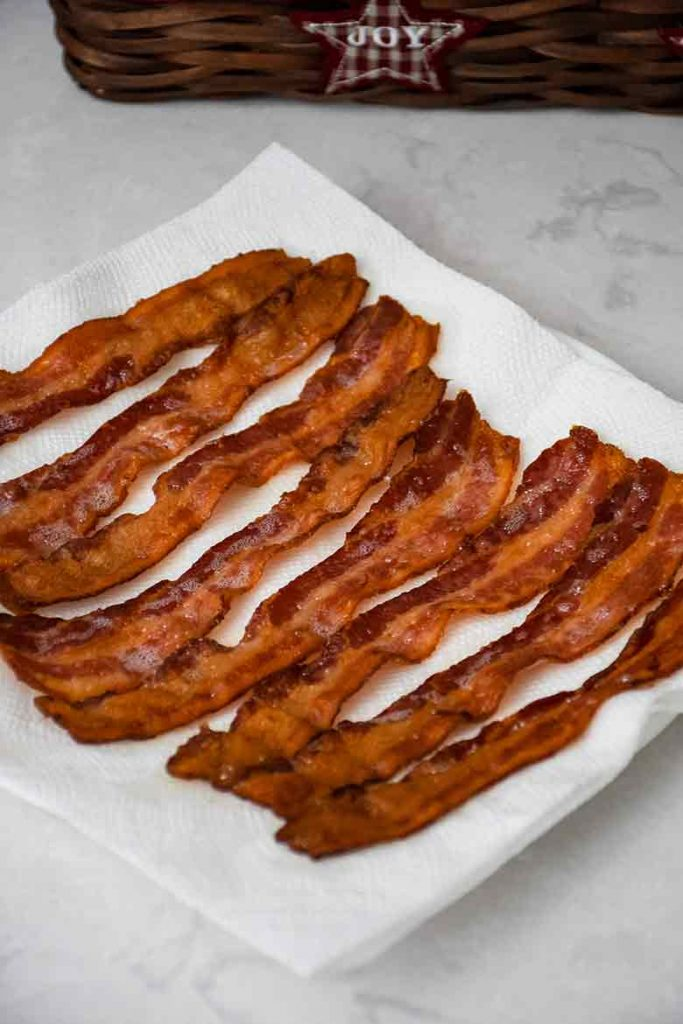 Cooked Bacon for recipe draining on a paper towel lined plate
