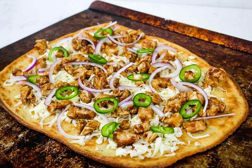 low carb pizza crust with cheese, bbq chicken, jalapeno, and onions ready to put in the oven to finish baking