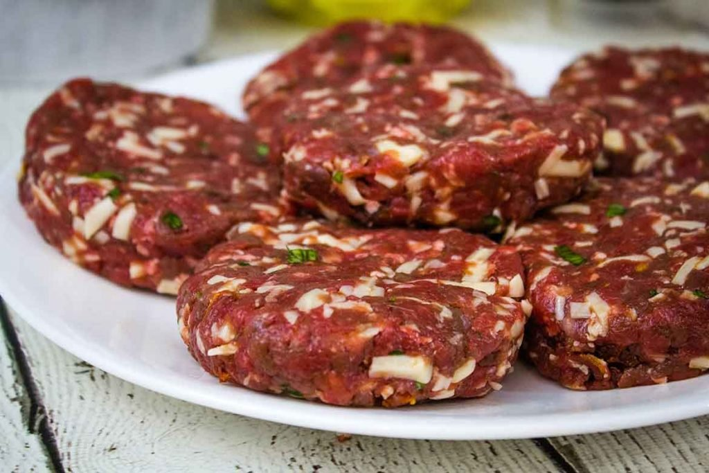 uncooked and fully assembled venison burger recipe on a white plate ready to grill