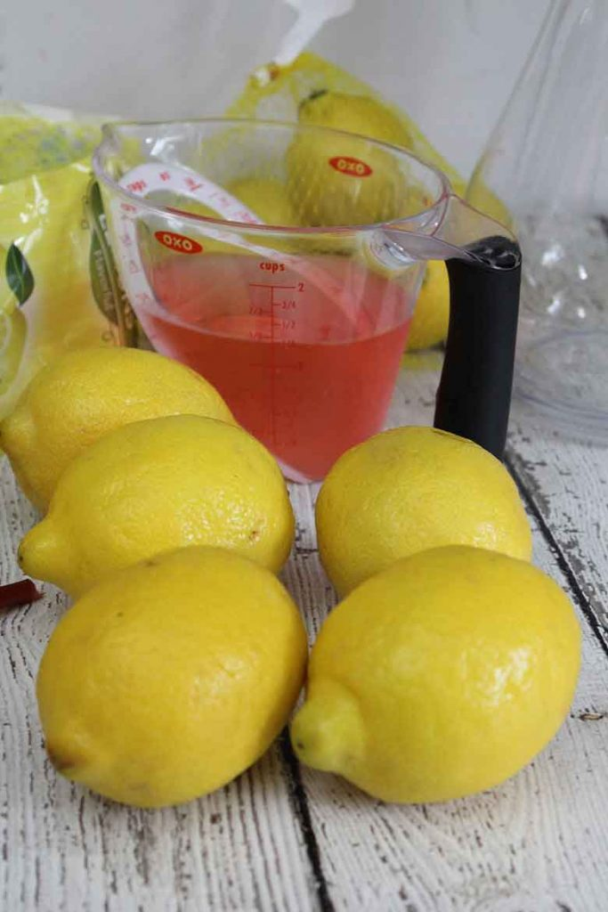 Fresh lemons in the foreground with a measuring cup of rhubarb syrup in the background