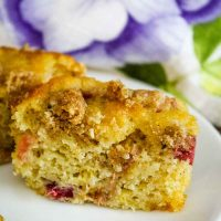 A Rhubarb Muffin with Crumb Topping cut in half on a white plate