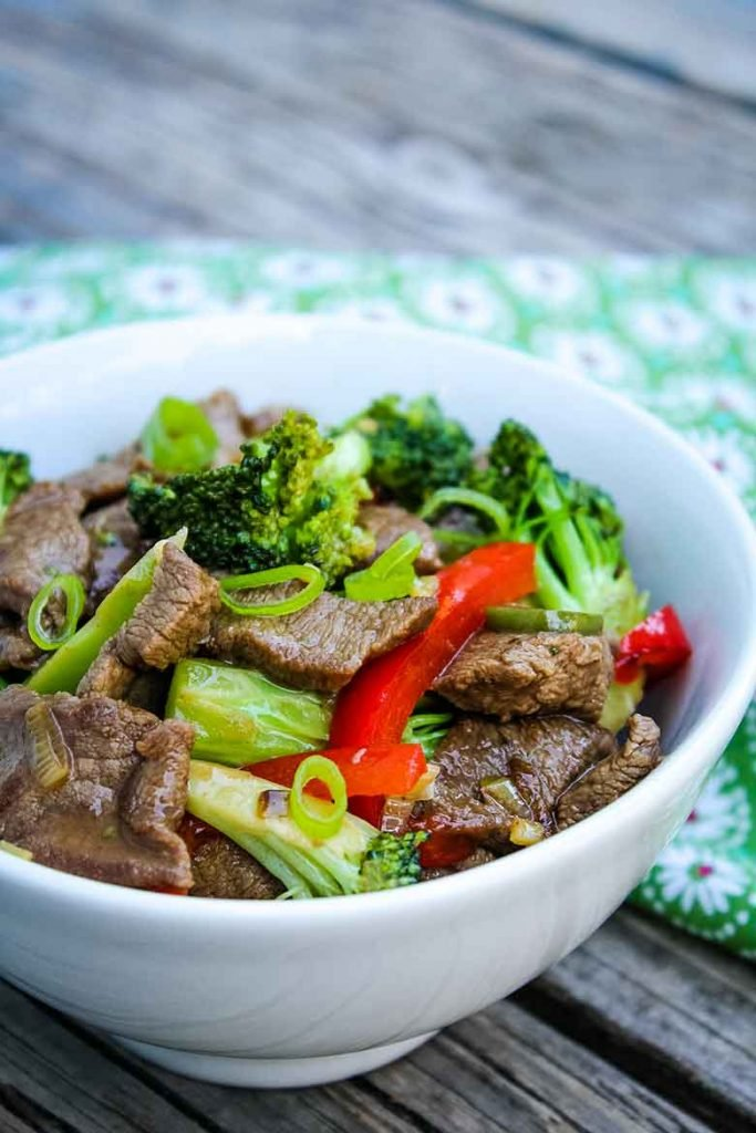 Spicy Venison Stir Fry Recipe in a white serving bowl with a green napkin in background