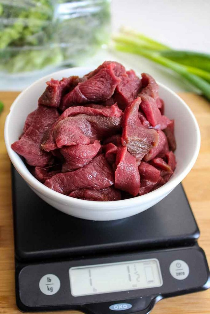 Thinly sliced venison steak in a white bowl on a scale weighing a little over a pound
