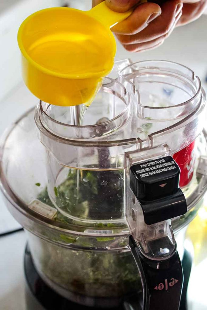 streaming the olive oil into the food processor
