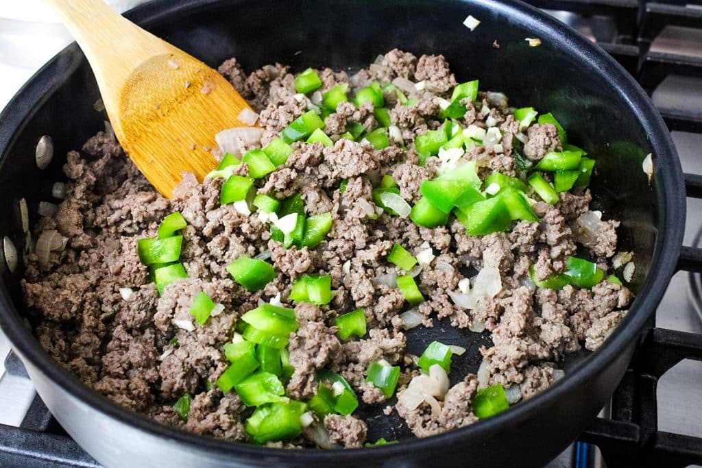 adding green pepper, garlic and water to venison sloppy joe recipe