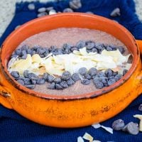 Chocolate Chia Pudding recipe in an orange bowl with coconut and chocolate chips on top