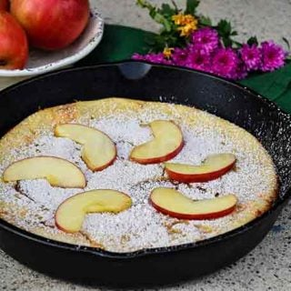 Apple Dutch Baby topped with fresh apple slices and whole apples in the background