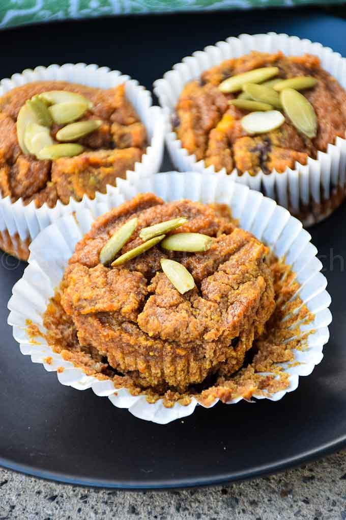 Paleo Pumpkin Muffins on a black plate with wrapper removed