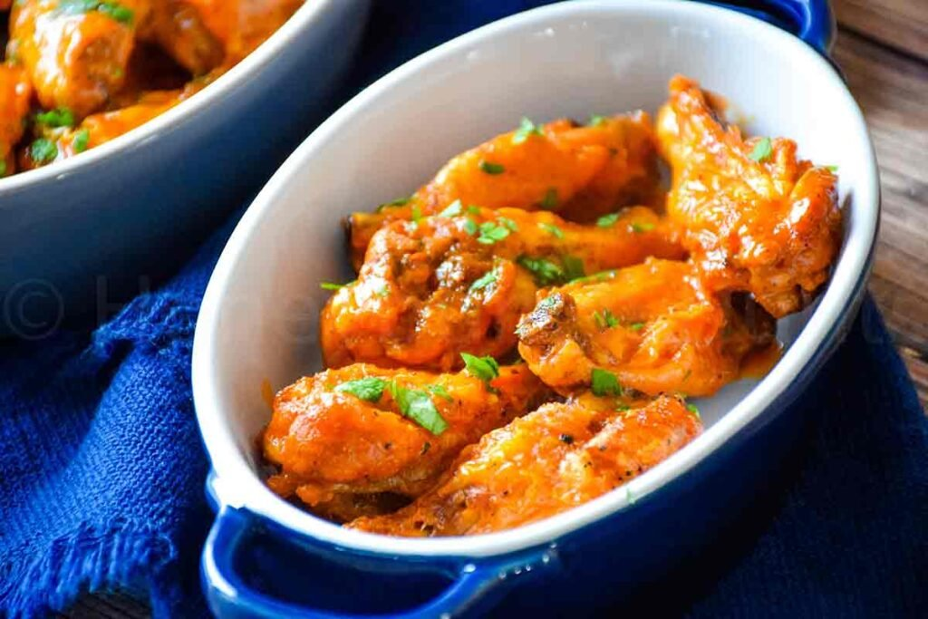 air fryer chicken wings with buffalo sauce in a blue serving dish