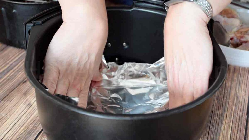 a pair of hands lining the fryer basket with foil