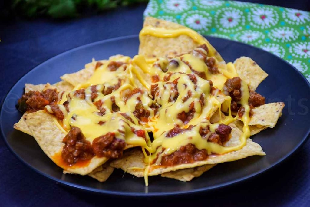 tortilla chip, venison chili, and melted cheese layer