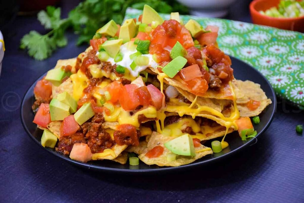a plate of loaded nachos with cilantro and a napkin in the background