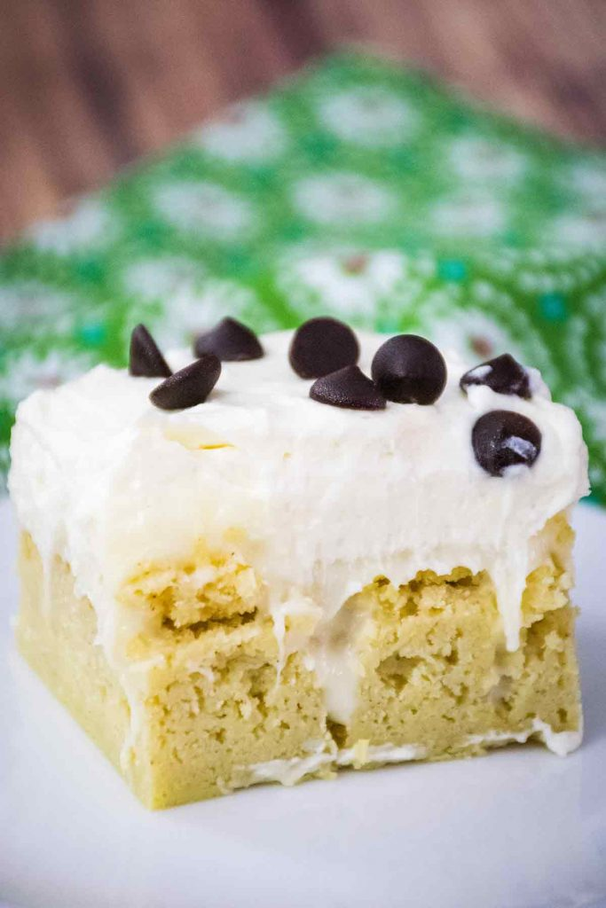 Keto Cannoli Poke Cake on a white plate with a green flowered napkin in the background