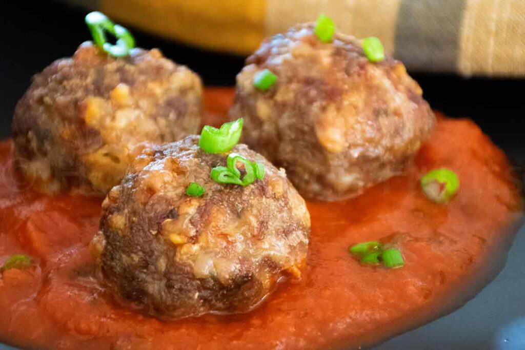 up close image of air fryer meatballs with pasta sauce on a black plate