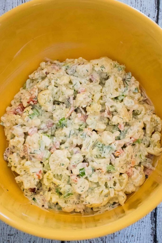 Keto Potato Salad mixed together with mayo dressing in mixing bowl