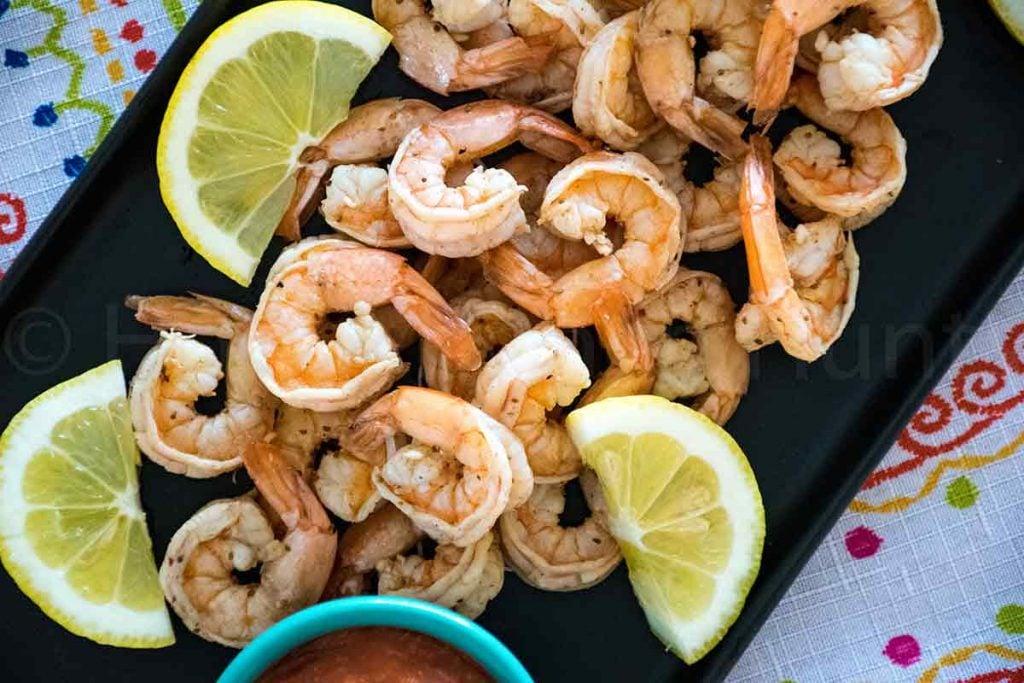 Old Bay Shrimp Boil on a black serving platter with lemon wedges and cocktail sauce.