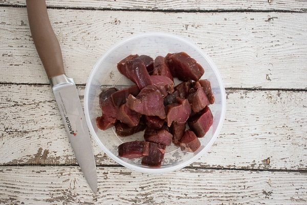 cut steak pieces in a white bowl with cutting knife to the left