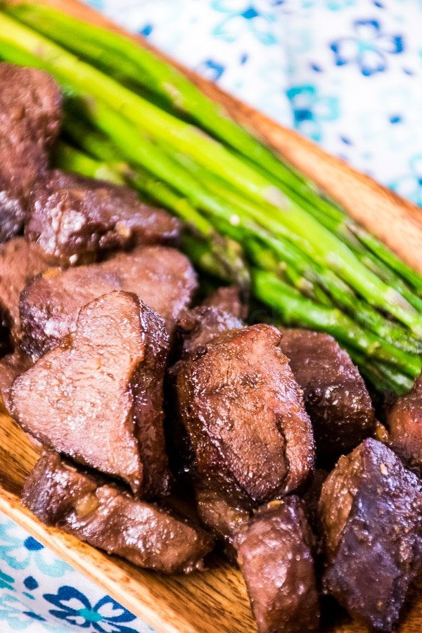 Venison steak bites on a acia tray with a side of asparagus