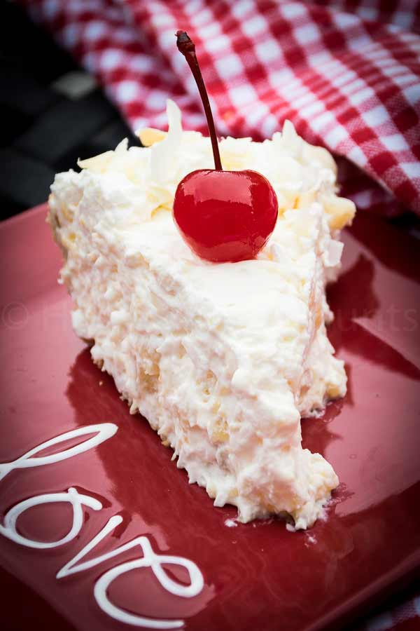A slice of Pina Colada Pie on a red plate with a cherry on top of the pie slice.
