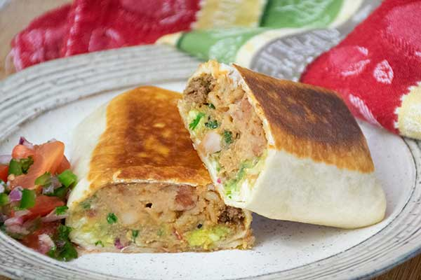 A grilled stuffed burrito with homemade taco meat inside