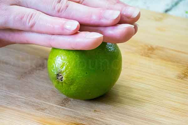a pair of hands rolling a lime on a cutting board