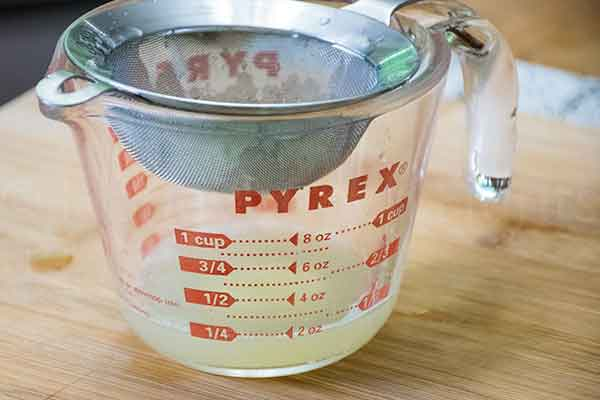 a measuring cup with a strainer to strain the lime juice