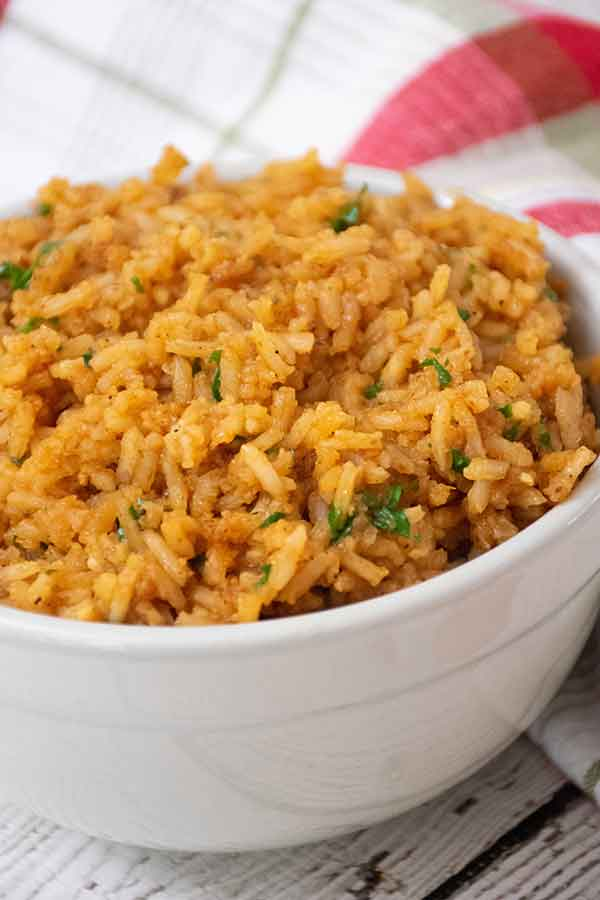 A white bowl full of Spanish rice with cilantro stirred in