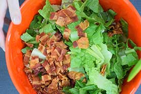 toss pasta, bacon, lettuce in bowl
