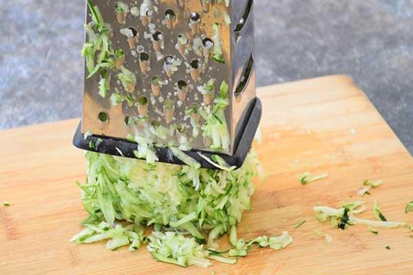 Shredded Zucchini in a box shredder on a wooden cutting board