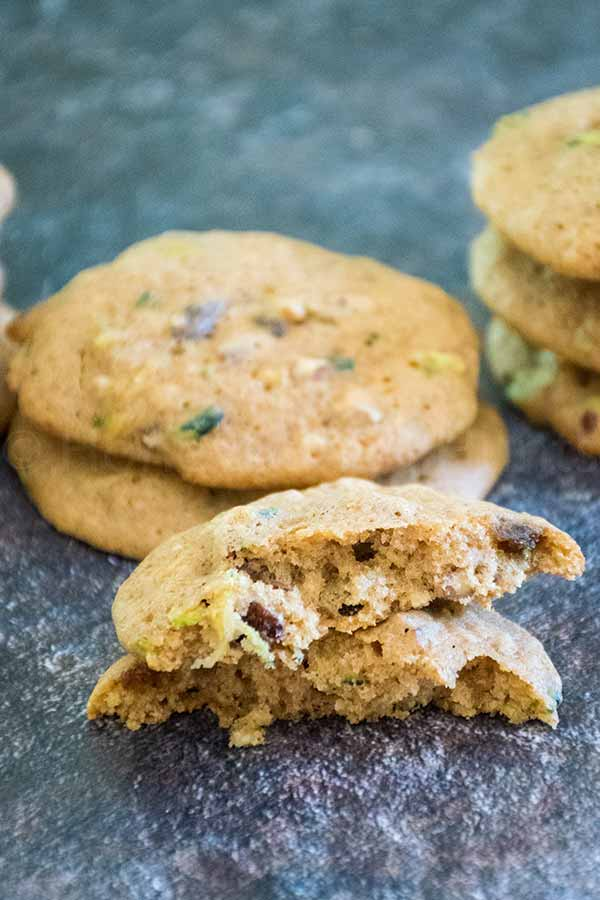 a pile of zucchini spice cookies with raising and walnuts with one cookie broken in half
