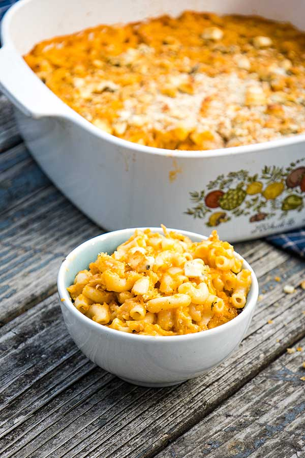 A serving of buffalo chicken mac and cheese in a bowl with the casserole dish in the background