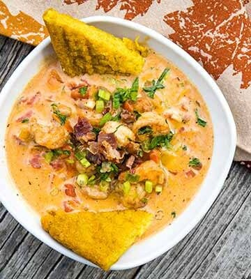 Cajun Shrimp with creamy tomato sauce in a white bowl with a tan napkin printed with fall leaves in the background