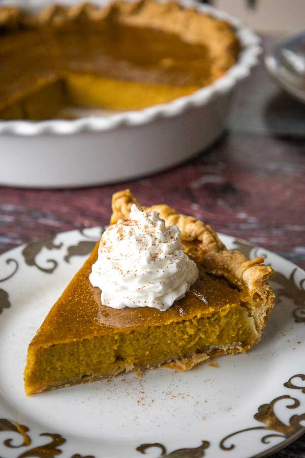 One slice of Maple Pumpkin Pie with whipped cream topping and the pie plate in the background