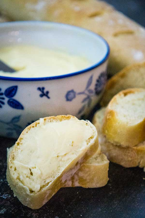 Slices of bread with salted maple butter spread on them and the dish of butter in the background