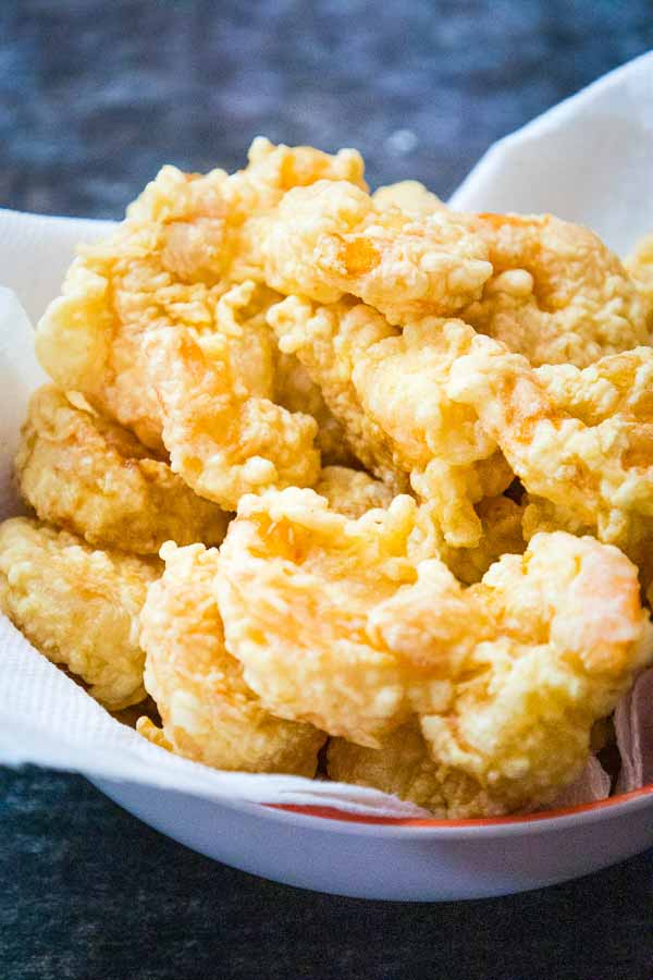 crispy fried shrimp draining on a paper towel in a bowl