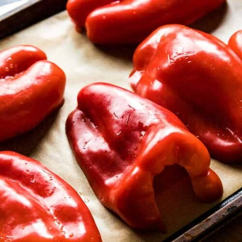Halved Red Peppers on parchment lined baking sheet