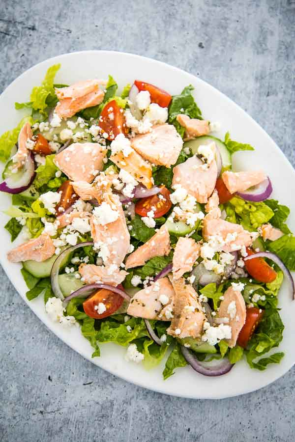 Overhead view of Greek Salmon Salad made with lettuce, cucumbers, tomatoes, flaked roasted salmon, and italian vinaigrette.