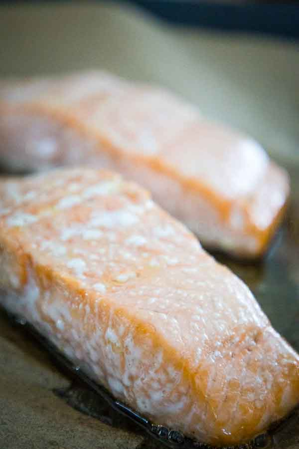 Two baked salmon fillets on a parchment lined baking sheet