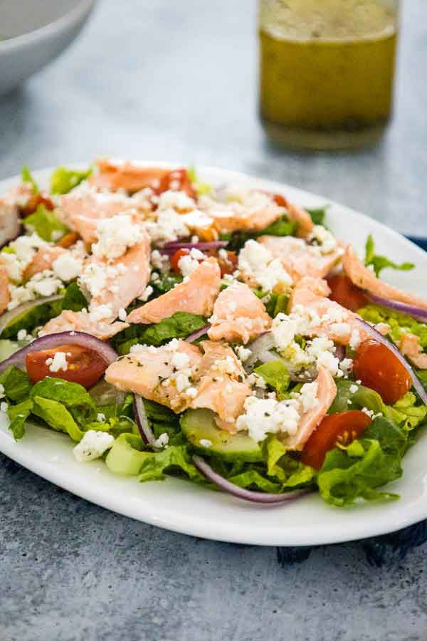 Greek Salmon Salad on a white plate with a bottle of vinaigrette in the background.