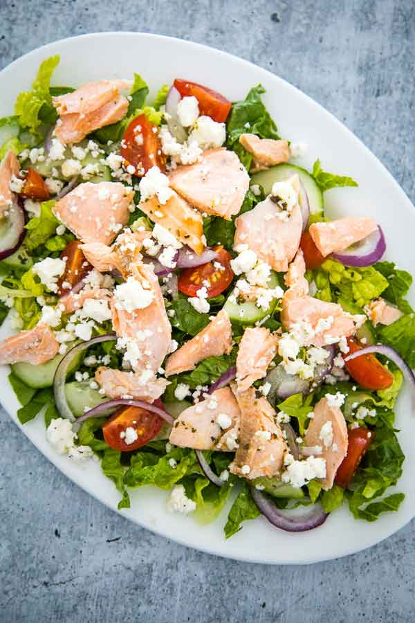 Overhead view of Greek Salmon Salad on a white plate.