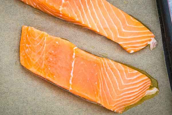 Two salmon fillets on a parchment lined baking sheet with olive oil rub.