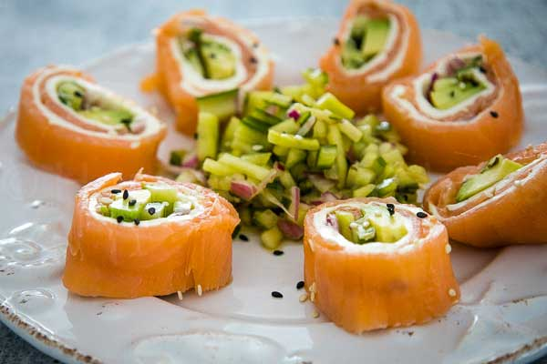 a plate with salmon sushi rolls